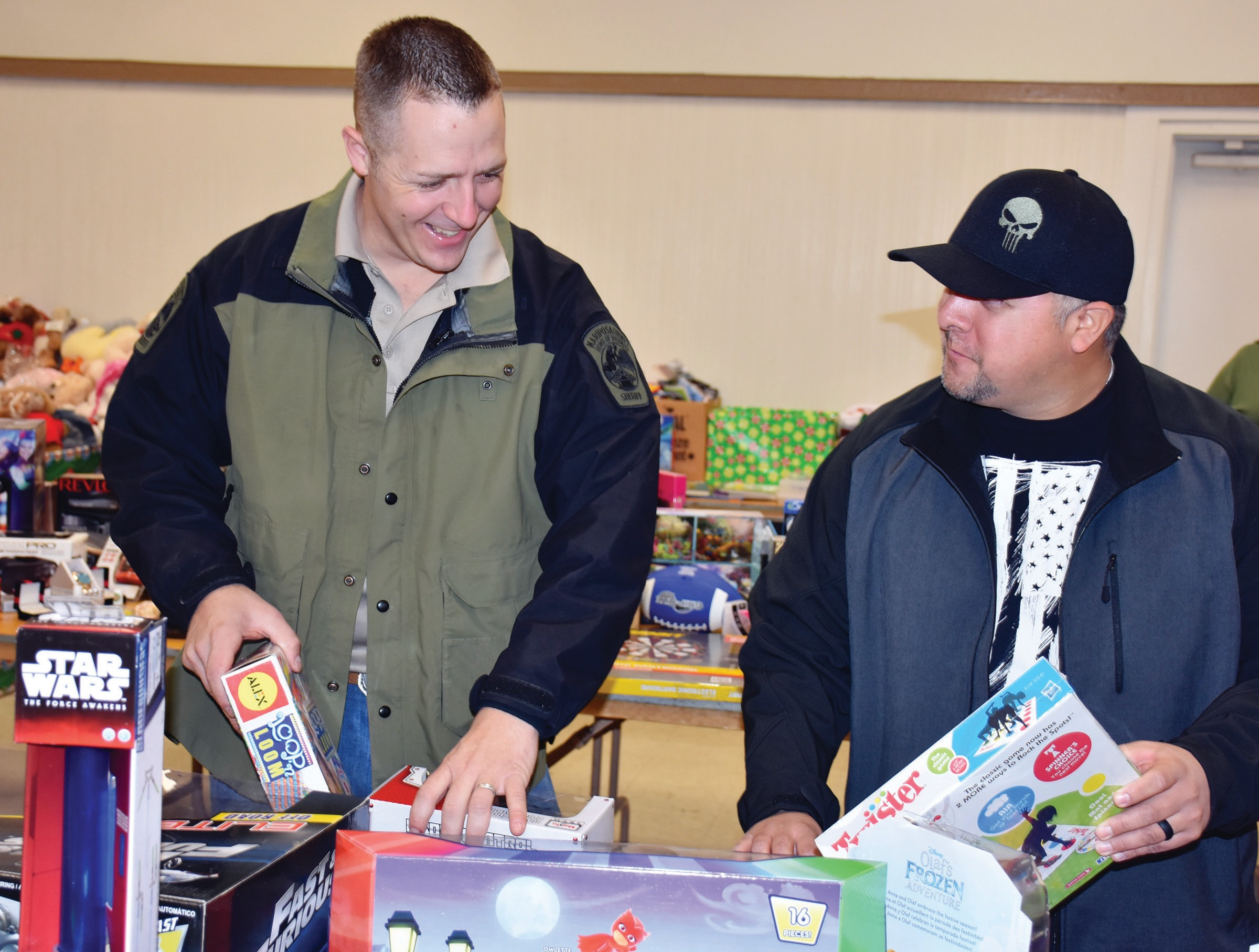 Deputy Will Atkinson, left, and Deputy Chris Boehm of the Mariposa County Sheriff's Office put the final touches on straightening toys during the Kops for Kids event last Saturday at the fairgrounds. Photo by Nicole W. Little