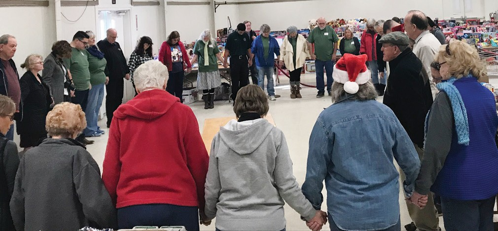 All of the volunteers gathered for a moment of prayer just before giving toys, clothes, food and more during Kops for Kids last weekend at the fairgrounds. Photo by Greg Little