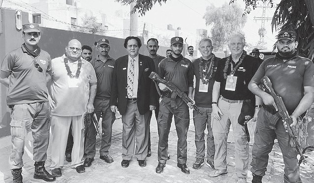 """Shown with the Rotarians are the armed police escort who Bill Lowe says """"allowed us to break all traffic laws to get through"""" the city of Lahore, Pakistan. Submitted photo"""