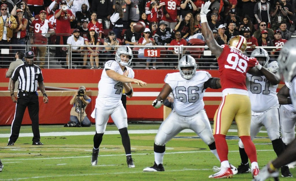 Raiders quarterback Derek Carr (4) throws a pass against the San Francisco 49ers during the 2018 season. The Raiders will play in Las Vegas beginning in 2020 but don't have a home site selected for the 2019 season. There are rumors the team could relocate to San Francisco for a year, or possibly even San Diego or Fresno. Right now, no one seems to be sure. Many Raider fans are disappointed in the situation. Photo by John Mabon