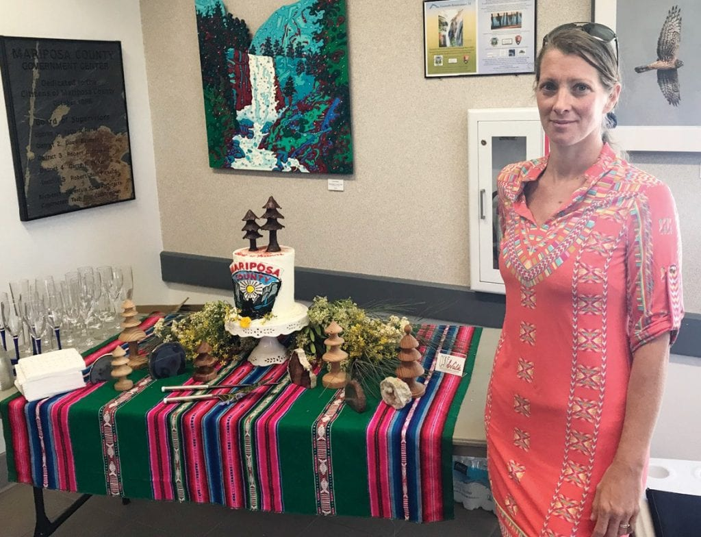Jennifer Ladd-Zimmerman of Cakewalk Heirloom Baking Co. in Coulterville shows off the cake she made for the unveiling of the new brand for Mariposa County. Below right is the proposed new logo for the county. On the left is one of the designs for a possible county seal. Photo by Greg Little