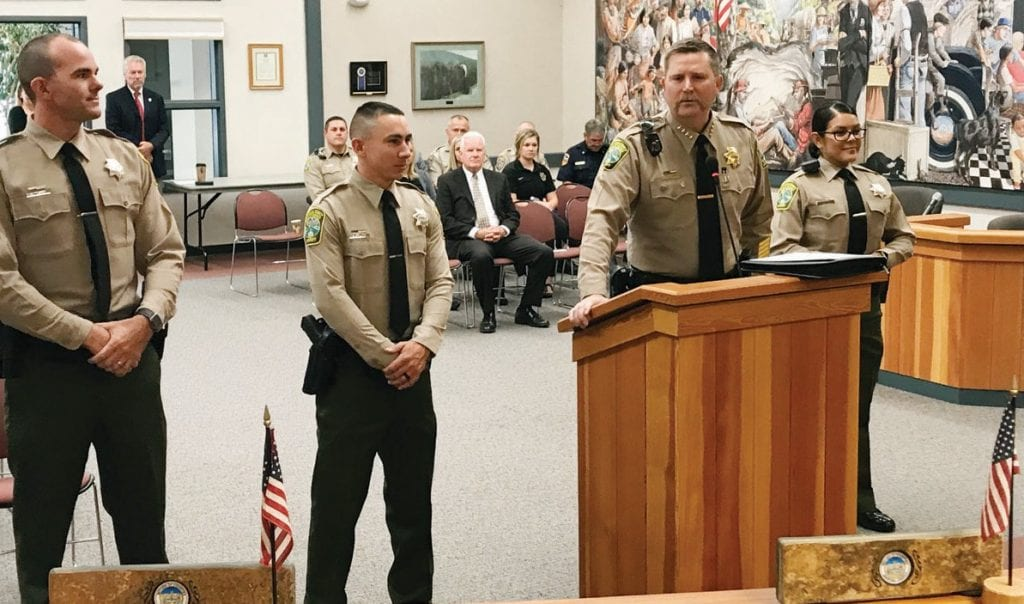"""Mariposa County Sheriff Doug Binnewies (at the podium) welcomed three new deputies to the department last week. He introduced them during the weekly Mariposa County Board of Supervisors meeting. From left are Will Tucker, Caleb Collins and Amber Rodriguez. """"I couldn't be more proud of the caliber and quality of these three,"""" said the sheriff. Photos by Greg Little"""