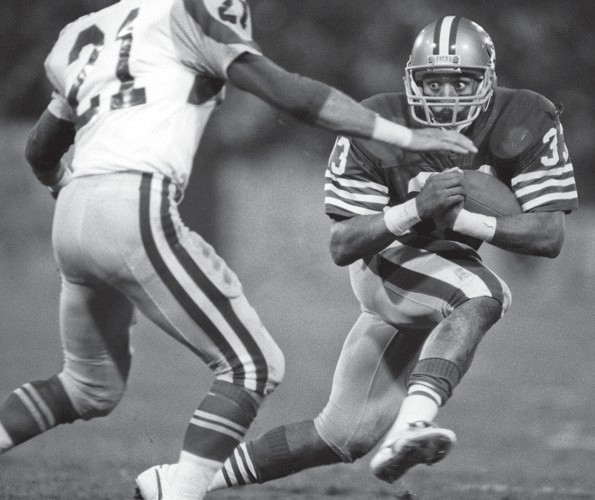 """San Francisco 49ers vs. Los Angles Rams at Candlestick Park Monday, Dec. 9, 1985. The Rams beat the 49ers 27-20. Los Angles Rams defensive back Nolan Cromwell (21) closes in on San Francisco 49ers running back Roger Craig (33). """"I just love to photograph Roger Craig's eyes,"""" Golub said. Golub used a 180mm F2.8 lens for this shot. """"We could stand a little closer in those days,"""" he said."""