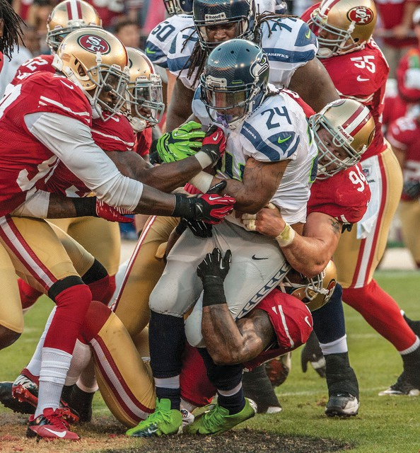 """San Francisco 49ers defensive end Justin Smith (94) tackles Seattle Seahawks running back Marshawn Lynch (24) at Candlestick Park in San Francisco. The 49ers defeated the Seahawks 13-6. Sports Illustrated used this shot. """"I've got the magazine somewhere,"""" Golub said. """"Marshawn is difficult to photograph because he has a dark shield and keeps his head down."""""""