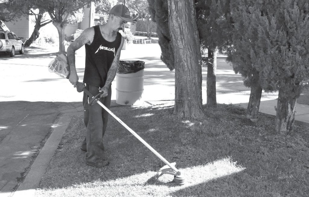 Matthew Klockars is shown weedeating at the Mariposa Fairgrounds. Much work goes into preparing for the fair every year. Photo by Matt Johnson