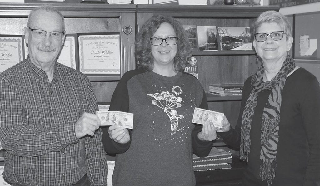 Nicole W. Little, center, gives $200 to Laura Lynn and Tom Hays, winners of the newspaper's first-ever Valentine's Day contest. Little is the publisher of the Mariposa Gazette. Photo by Greg Little