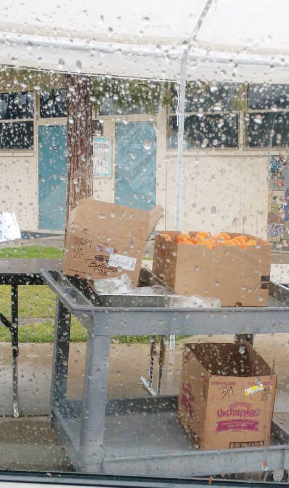 This photo taken through a rain covered car window of the Coarsegold Elementary distribution site of free school lunch on March 16. Schools in Madera County continue to assist families by offering meals. Photo by Kellie Flanagan