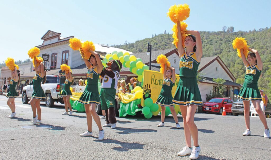 Alongside the marching band, the Mariposa County High School cheerleaders — with their mascot, of course — stopped during their march down to perform their routine before the Lions Club members and the parade judges. Photo by Christina Manuel