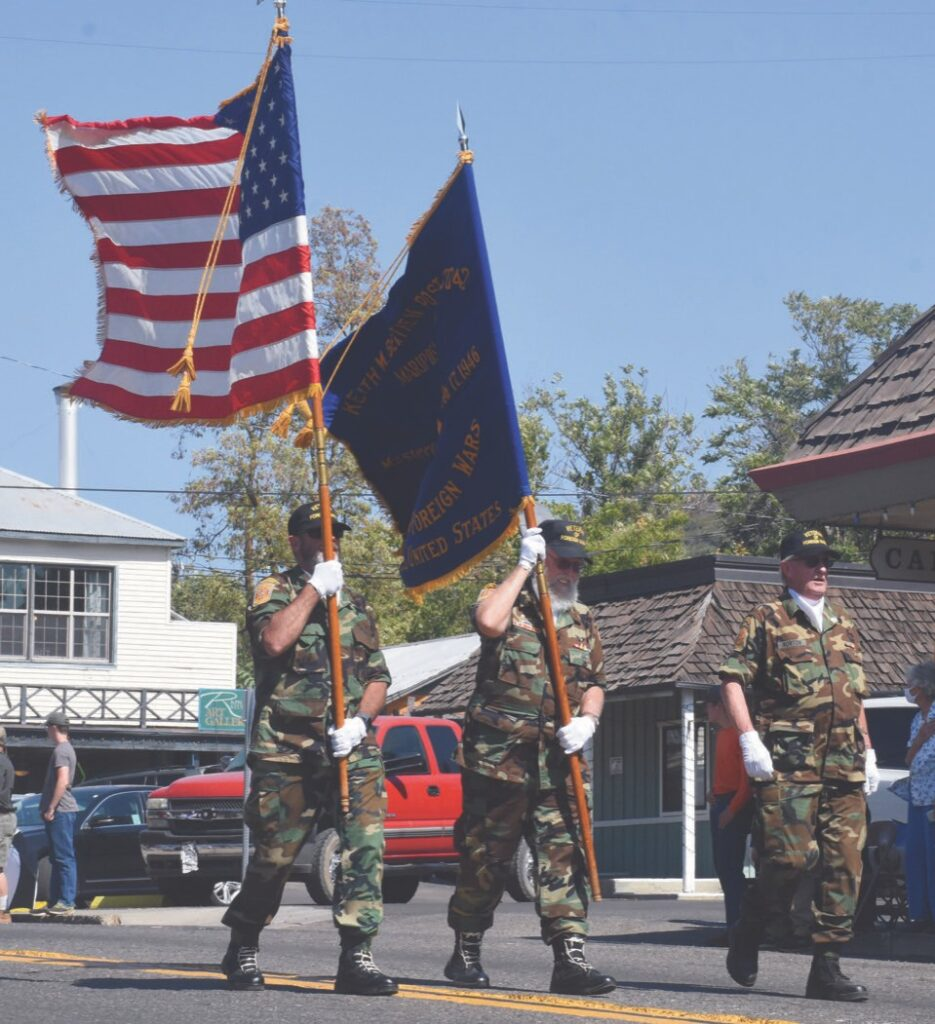 Colorguard members carry flags in front of all other floats at last weekend's Lions Club parade. Photo by Allen Laman