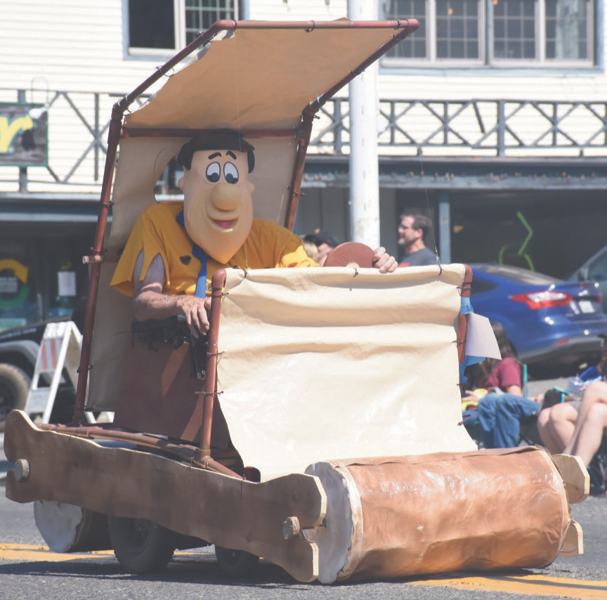 Ron Ritchie dressed as Fred Flintstone and piloted a float resembling the Cavemobile. Photo by Allen Laman