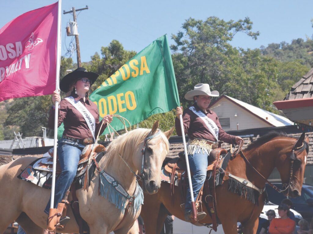 Tillyanna Healey (left) and Daniele Turck (right) carry Mariposa County Rodeo Royalty flags through downtown Mariposa on horseback. Photo by Allen Laman